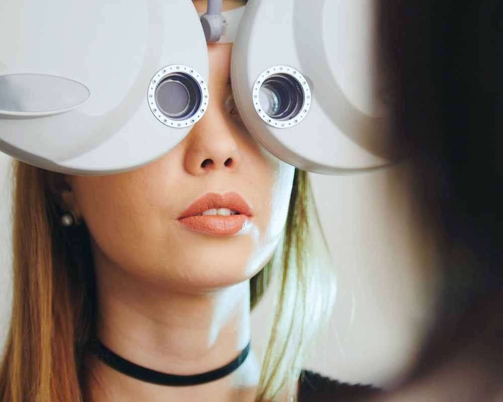 Woman getting an eye exam with optometry equipment