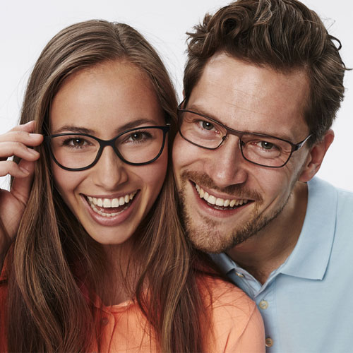 attractive male and female couple smiling with glasses