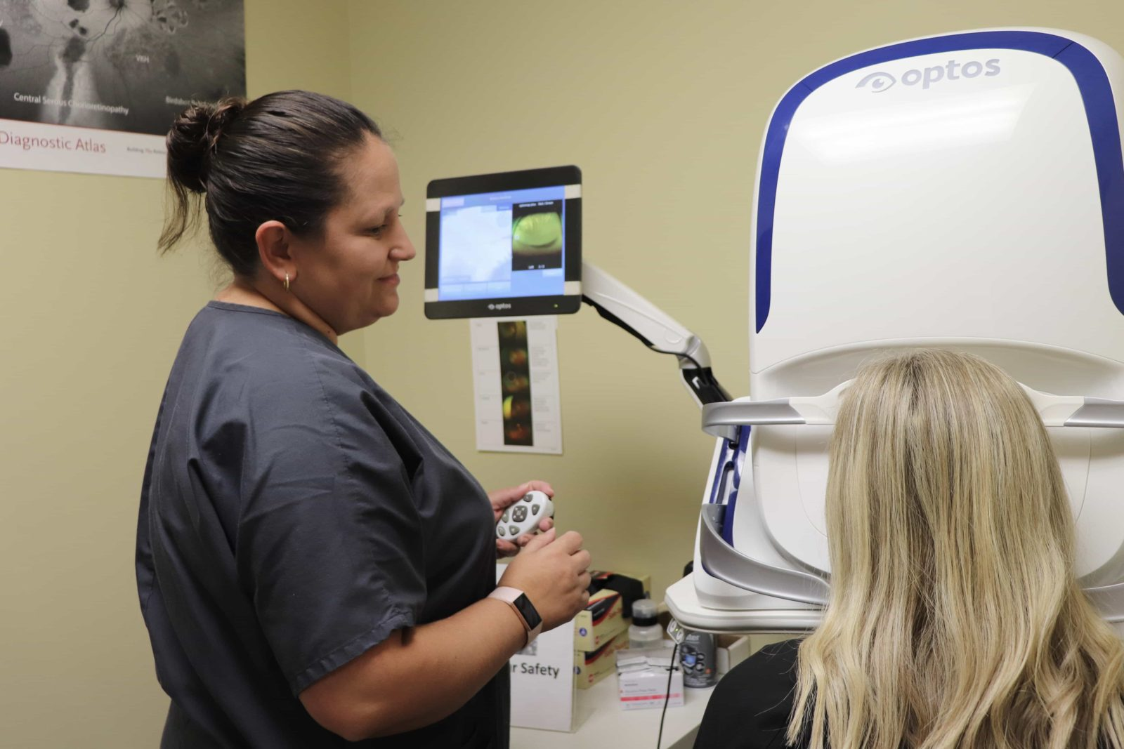 Staff member examining a patient via Optos machine
